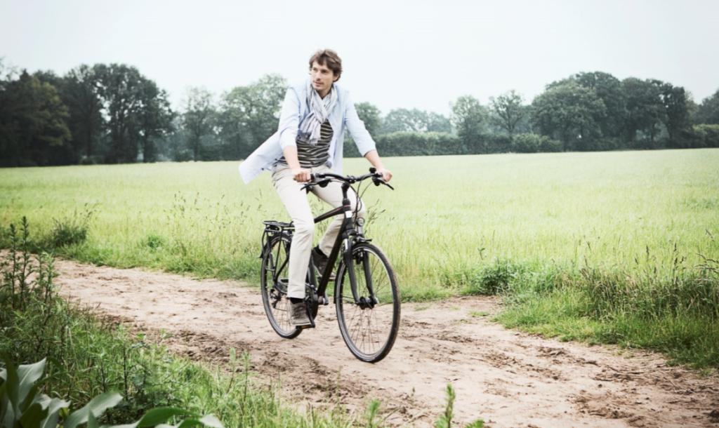 Homme sur un vélo de ville mixte à la campagne