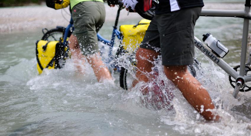 Deux cyclistes traversent une rivière à pied avec sacoches étanches jaunes