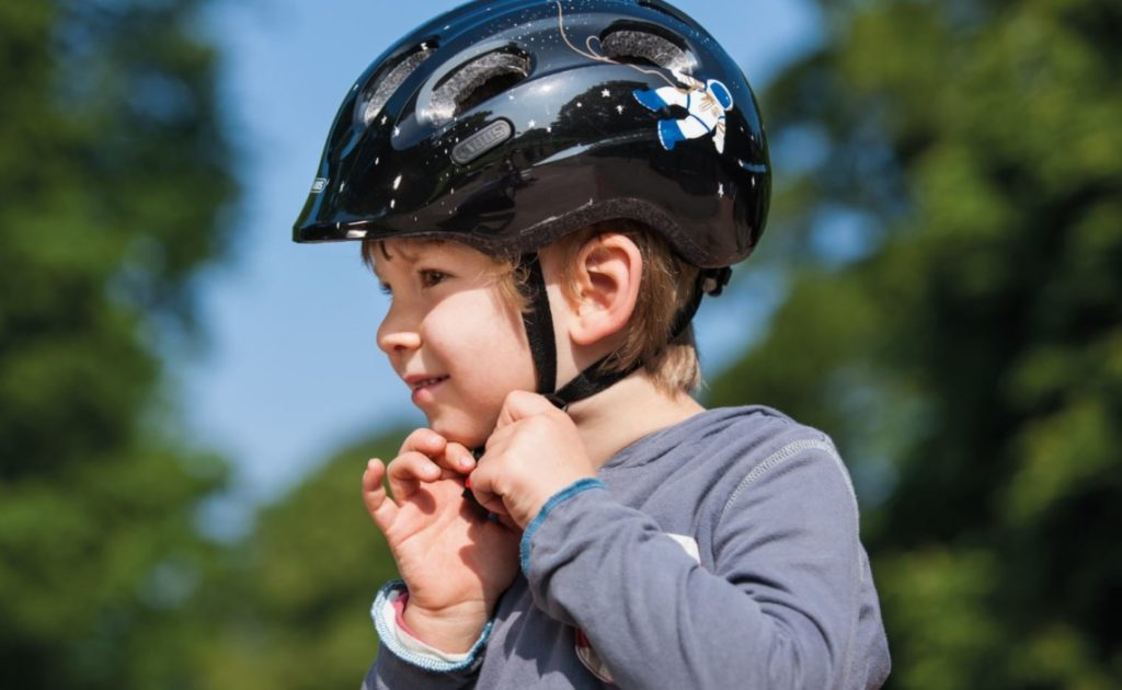 Enfant en train d'attacher son casque de vélo noir