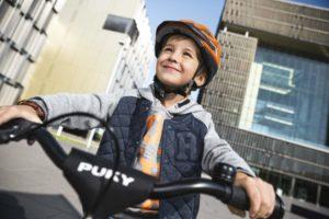 Enfant avec un casque souriant sur son vélo