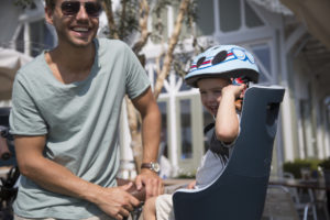 Enfant sur un siège vélo avec un casque et son père à côté