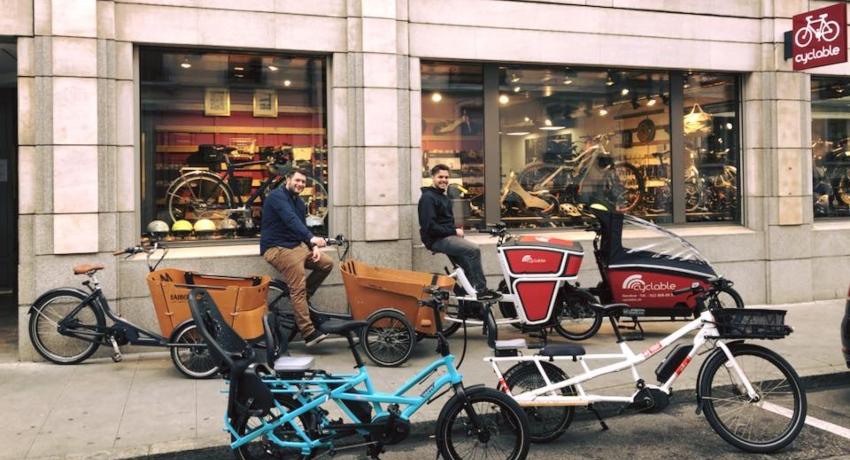 Equipe de Cyclable Genève Plainpalais devant le magasin sur des vélos cargos