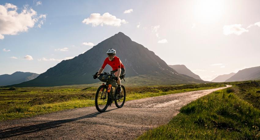 Cycliste roulant à vélo équipé bikepacking Apidura sur une route avec montagne en fond