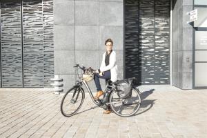 Femme à l'arrêt avec un vélo électrique