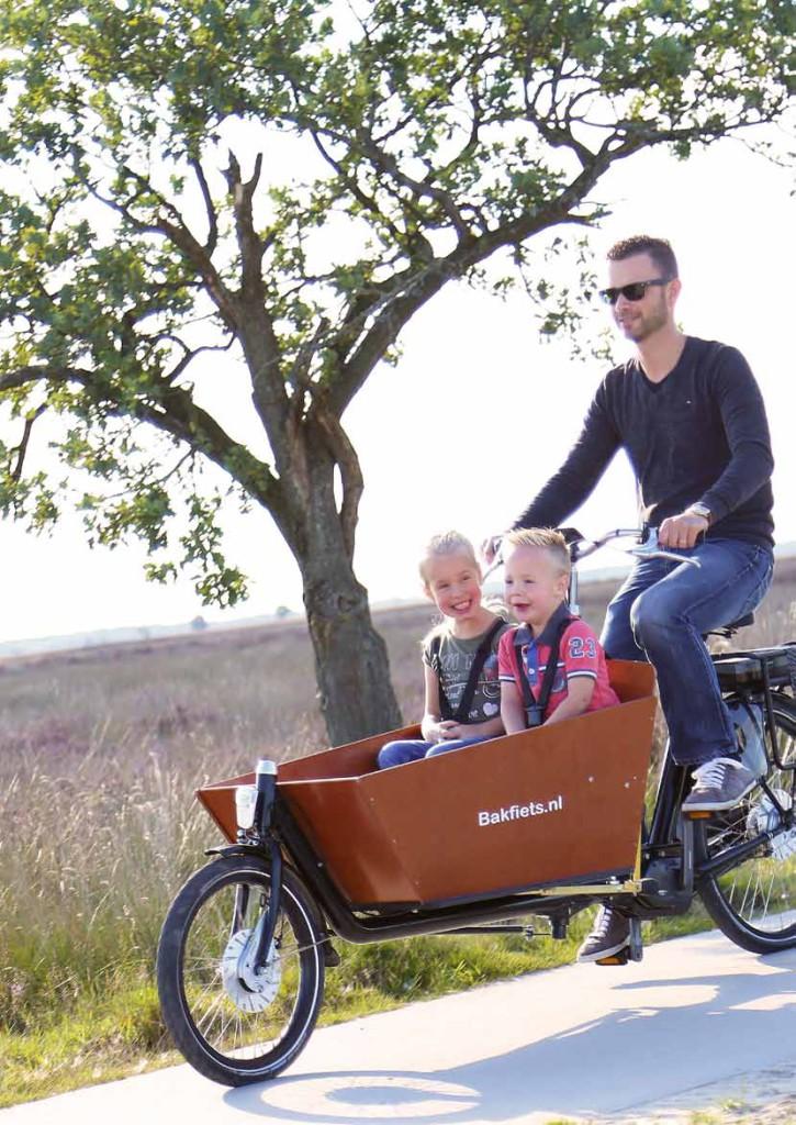 Père avec ses deux enfants sur un vélo cargo électrique