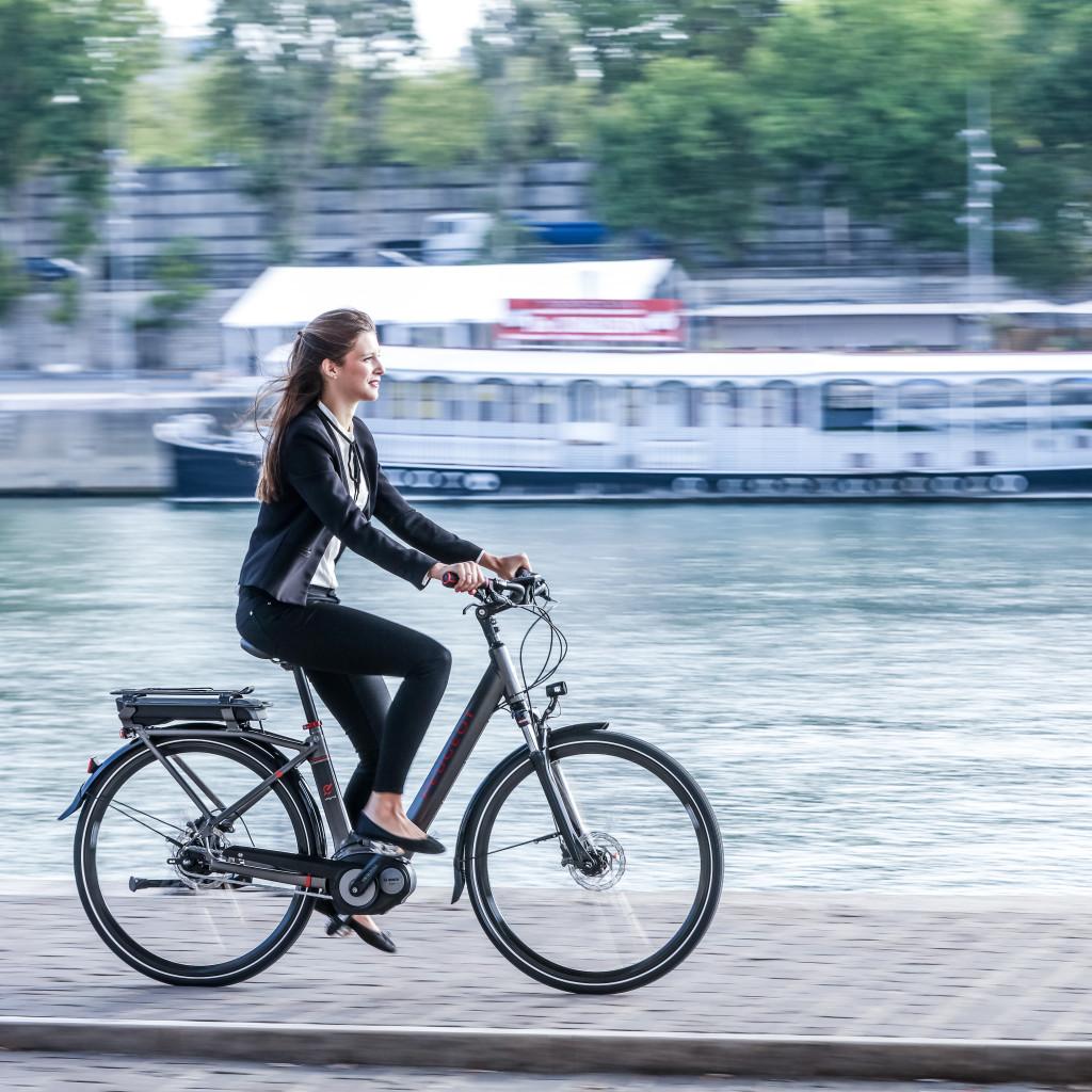 Jeune femme à vélo le long d'un fleuve avec péniche