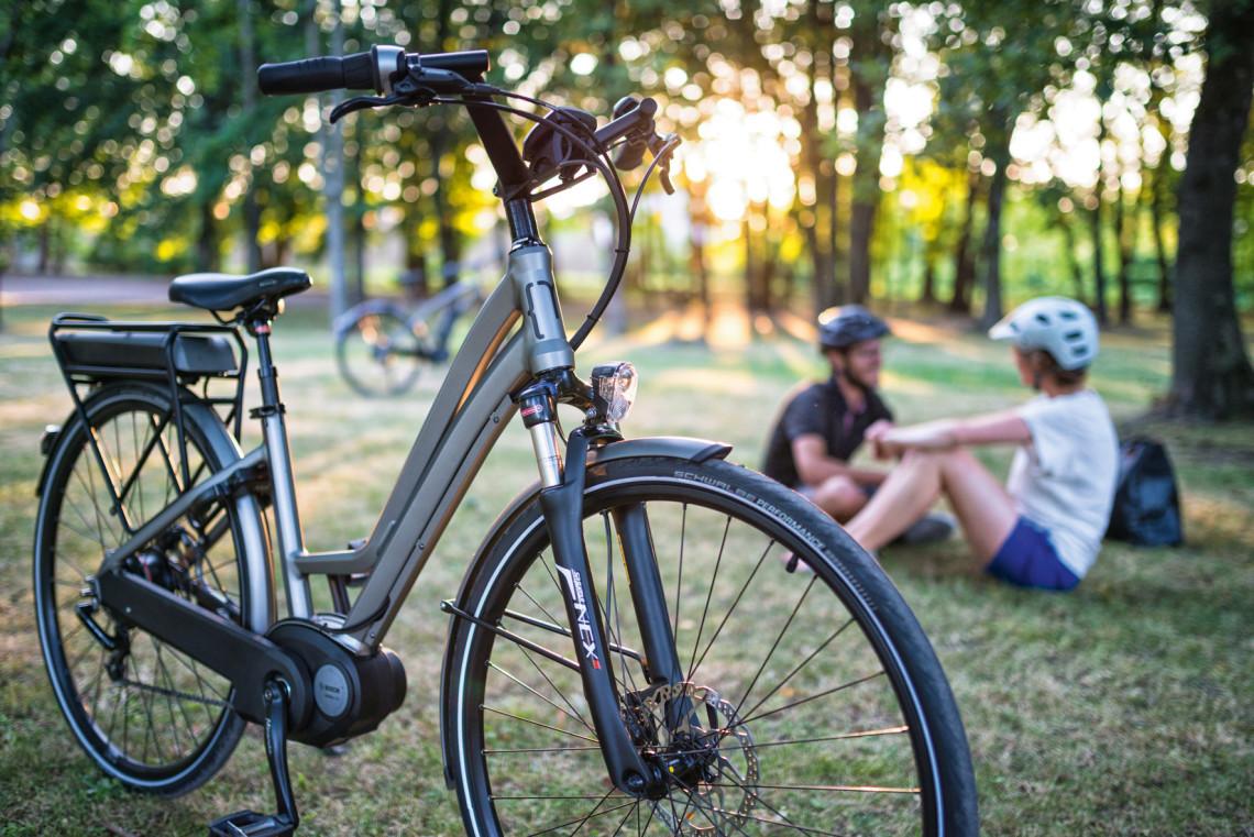 Cyclistes se reposant avec vélo électrique au premier plan