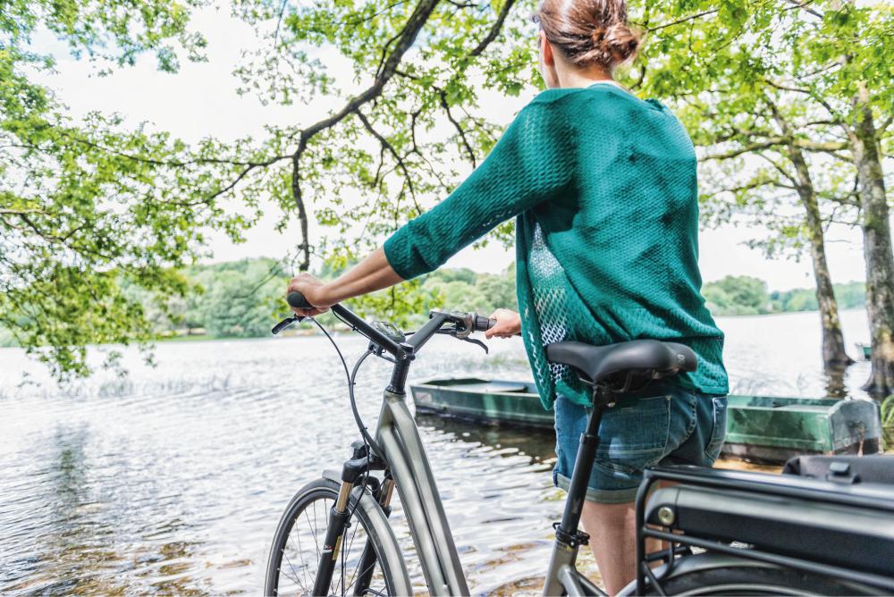 Femme avec un VTC à assistance électrique au bord d'un lac