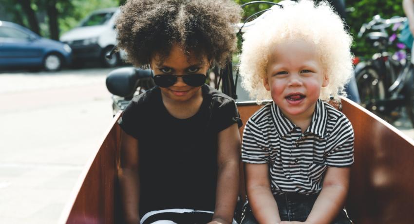 Deux enfants assis dans la caisse d'un vélo cargo