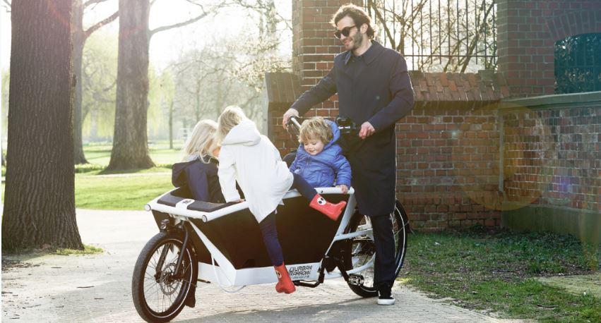 Père transportant ses 3 enfants sur un vélo cargo