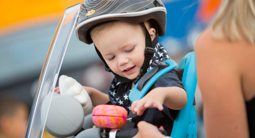 Bébé portant un casque sur un siège vélo avant