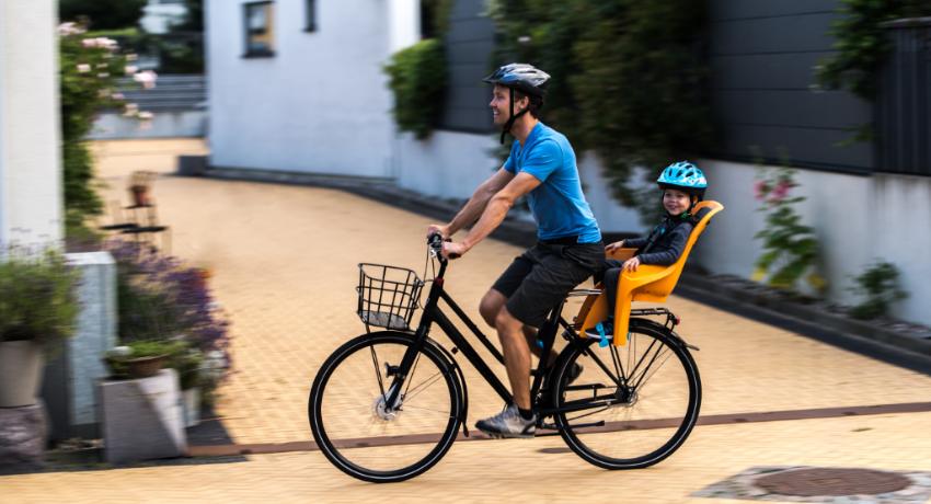 Papa qui roule à vélo avec son fils dans un porte-bébé