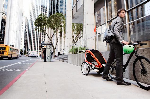 Père en train de poser son vélo avec une remorque