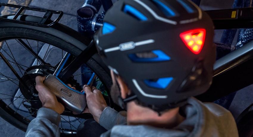 Cycliste attachant son vélo de nuit avec un antivol connecté
