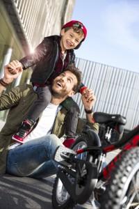 Père et son fils souriant devant un vélo enfant