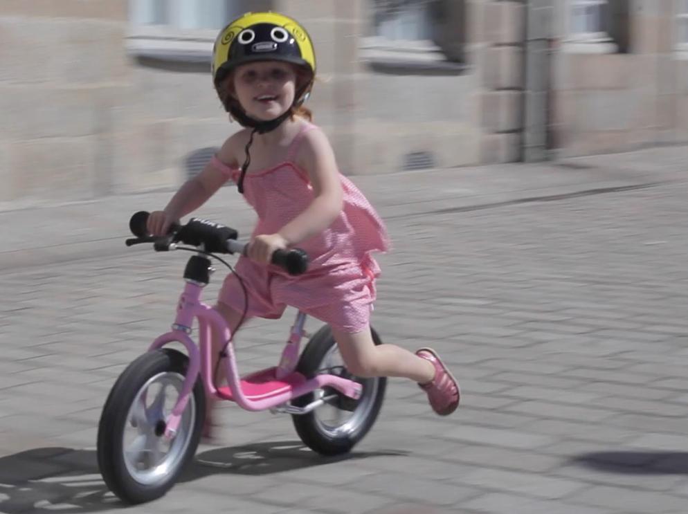 Petite fille roulant sur draisienne à vive allure