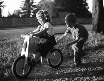 Deux enfant jouant avec une draisienne en bois