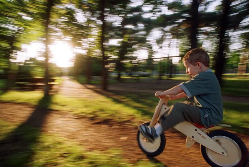 Enfant en plein élan sur vélo en bois