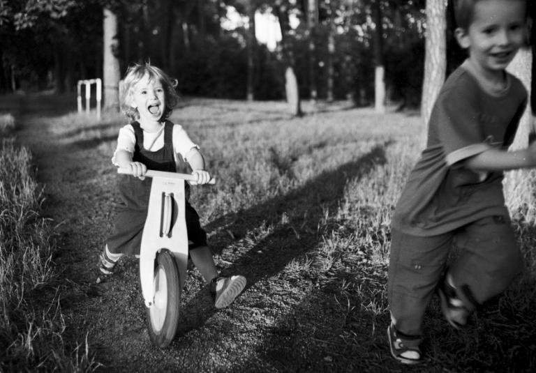 Deux enfants jouant avec un vélo en bois