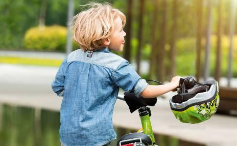 Enfant poussant un vélo vert