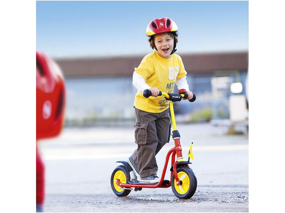 Enfant sur une trottinette rouge puky