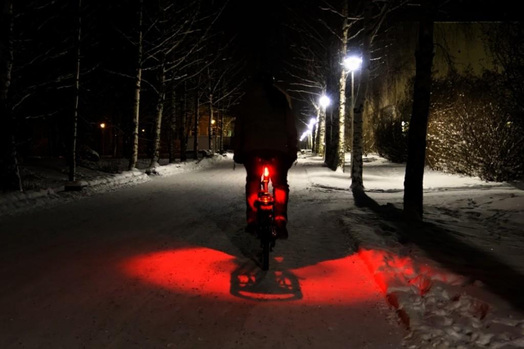 vélo qui s'éloigne de nuit et dans la neige en ville
