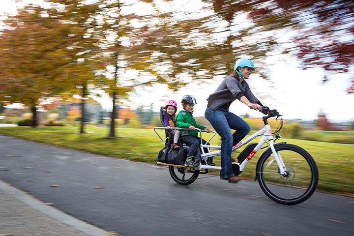 Mère et ses deux enfants en train de rouler un un vélo cargo yuba électrique