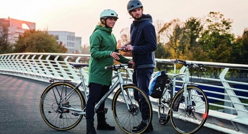 Deux cyclistes à pied près de leur vélo en hiver