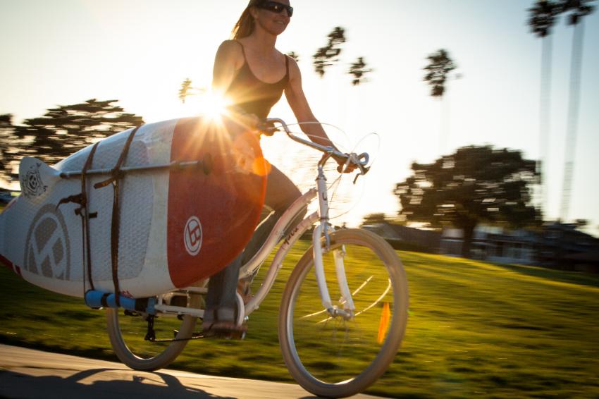 Femme sur un vélo Yuba transportant un surf