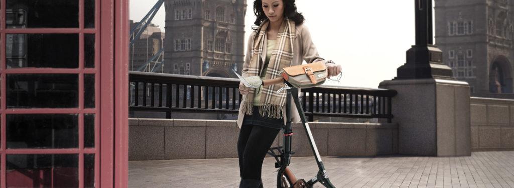 Femme accoudée sur un vélo pliant strida