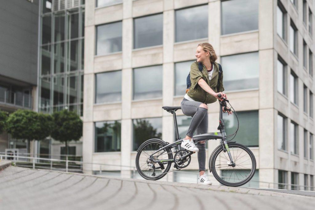 Jeune femme sur un vélo pliant à l'arrêt