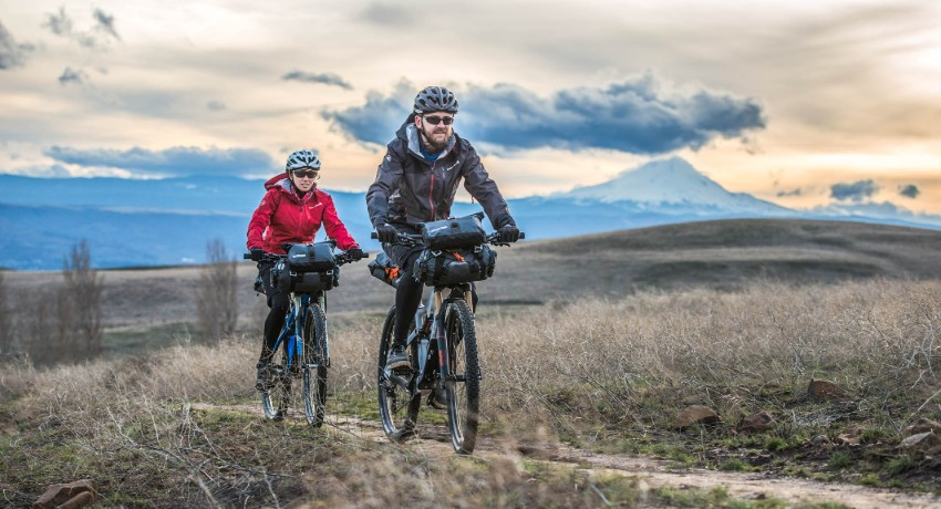 Couple cycliste en train de rouler en bikepacking