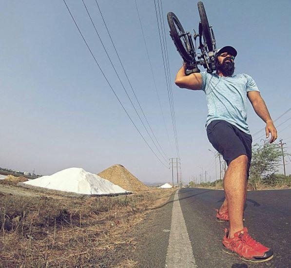 Homme portant un vélo pliant sur son épaule