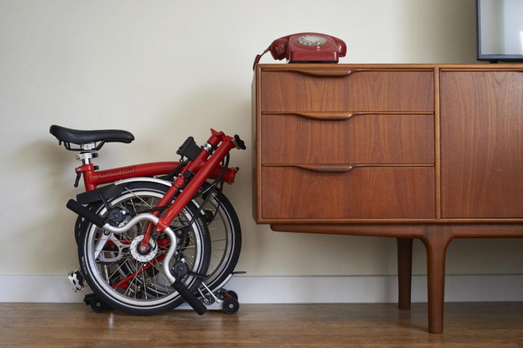 Vélo pliant Brompton plié dans un appartement