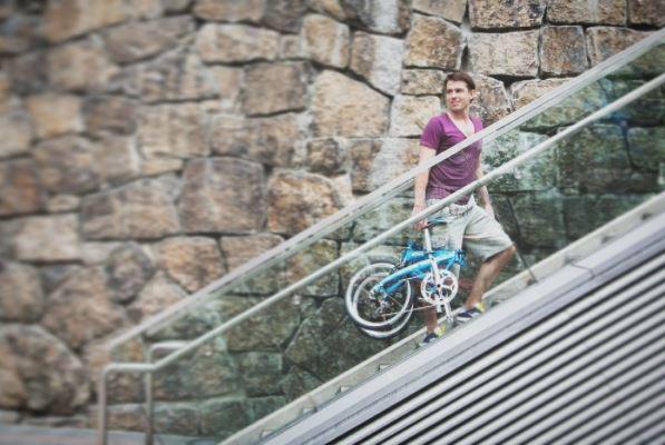 Homme portant un vélo pliant dans des escalators