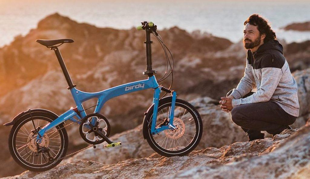 Homme accroupi près d'un vélo pliant bleu