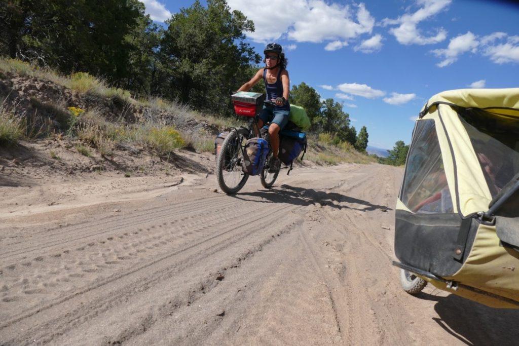 Famille à vélo roulant dans le sable