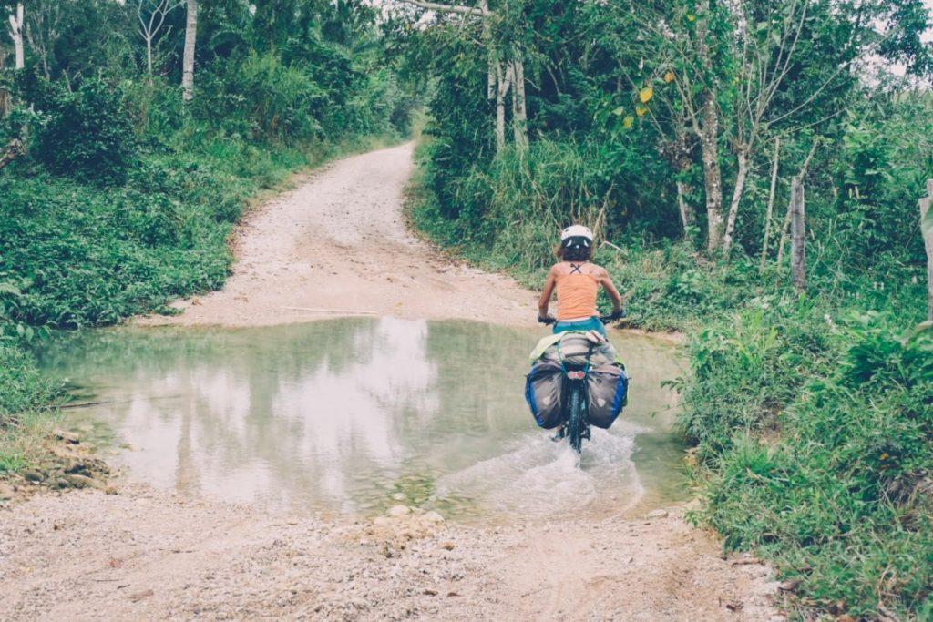 Femme à vélo traversant un gué