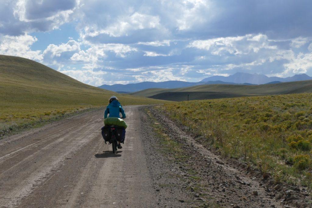 Femme cycliste en voyage à vélo s'éloignant sur la route