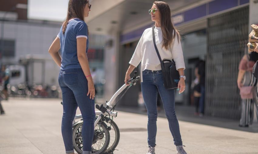 Deux femmes en train de parler près d'un Brompton electric plié