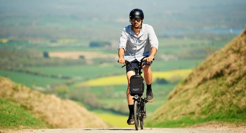 Cycliste qui monte une cote en Brompton électrique dans la campagne