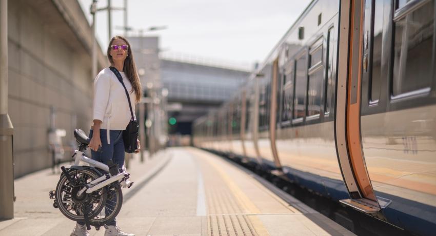 Femme qui va prendre son train et porte un vélo électrique pliant Brompton