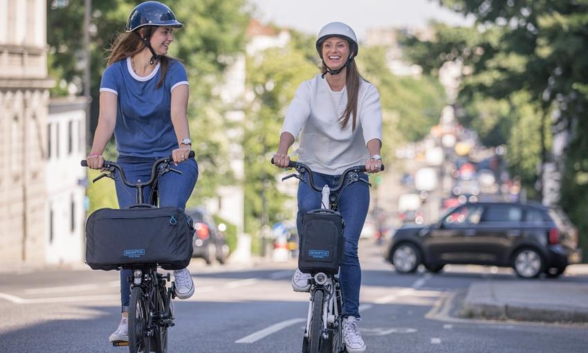 Deux femmes sur des vélos pliants électriques Brompton en ville