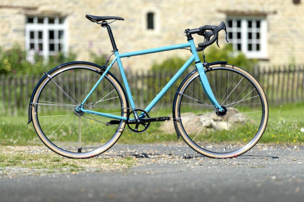 Vélo gravel Genesis Flyer 2018 bleu devant une maison de pierre