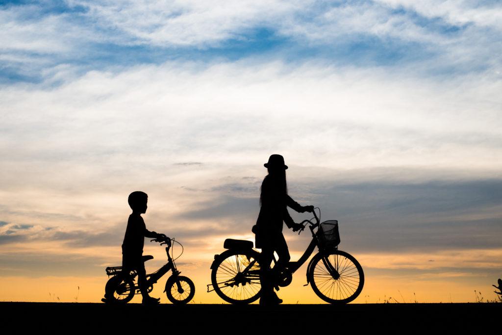 Coucher de soleil avec une femme et son fils à vélo