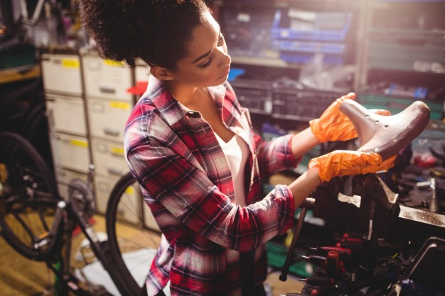 Femme qui examine une selle dans un atelier velo