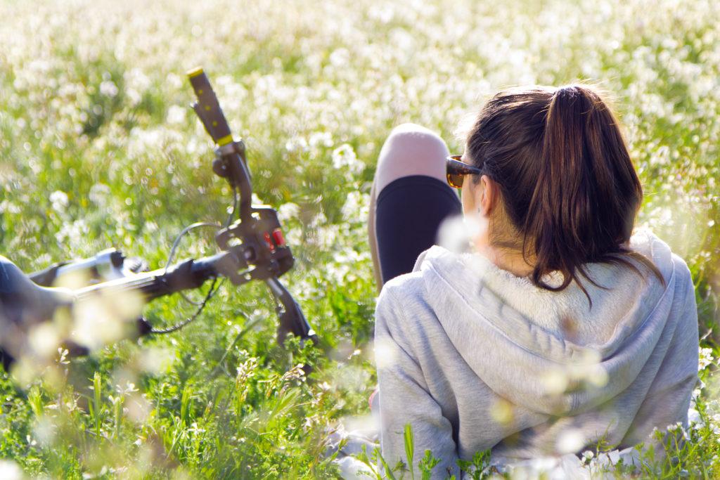 Femme allongé dans l'herbe près de son vélo