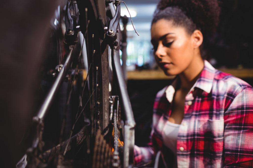 Femme qui répare son vélo