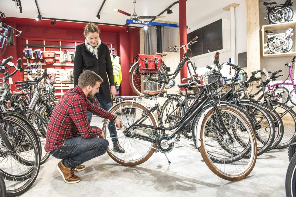 Vélociste qui répare le vélo d'une cliente cycliste