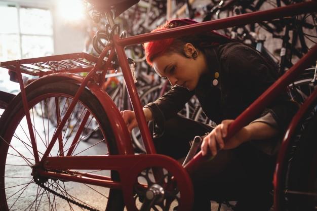 Mécanicienne en train de réparer un vélo de ville